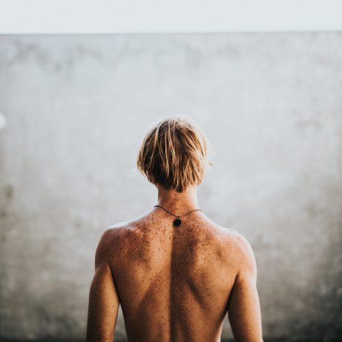 Ein Mann steht mit dem Rücken vor einer Wand.